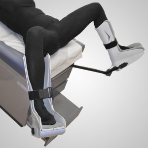 Model laying on table with feet rested in GStirrup with foam foot pads.